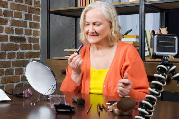 Blogger mujer mayor grabando haciendo su maquillaje en línea