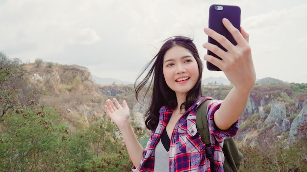 Blogger, mujer mochilera asiática, grabación de video vlog en la cima de la montaña, joven mujer feliz que usa el teléfono móvil para que el video vlog disfrute de las vacaciones en la aventura de senderismo.