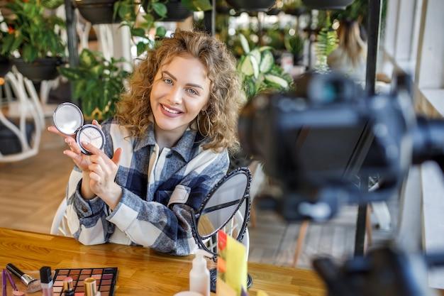 Blogger de mujer rubia está mostrando cómo maquillarse y usar cosméticos