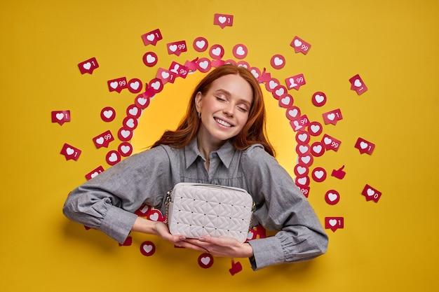 Blogger mujer sonriente optimista mostrando un nuevo bolso, esperando la reacción de la gente