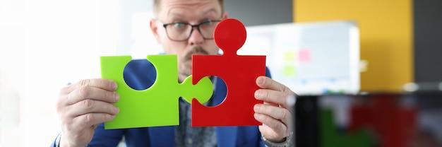 Blogger de negocios masculino conecta la búsqueda de rompecabezas coloridos para socios comerciales y soluciones
