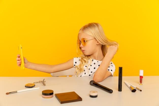 Blogger de niña pequeña en el estudio amarillo frente a cámara haciendo video. trabajando como blogger, grabando video tutorial para internet.