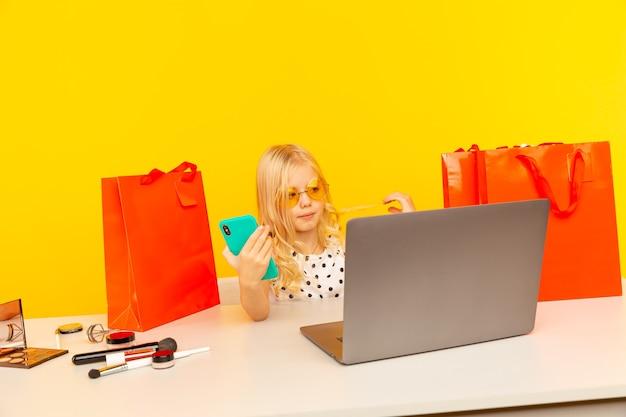 Blogger de niña con teléfono azul haciendo video para blog y seguidores sentados en el estudio amarillo aislado.