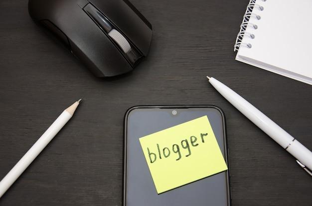 Blogger palabra en la pegatina ratón de la computadora con teléfono inteligente y lápiz en negro