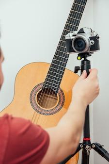 Blogger prepara la cámara de grabación para dar clases de guitarra desde su estudio de grabación en casa.