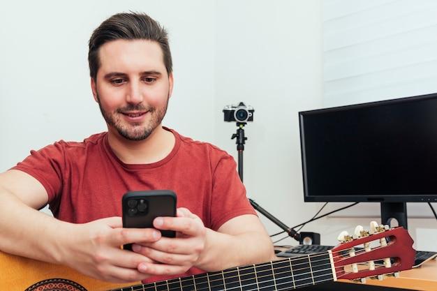 Blogger revisando su teléfono antes de dar la lección de guitarra desde su estudio de grabación en casa