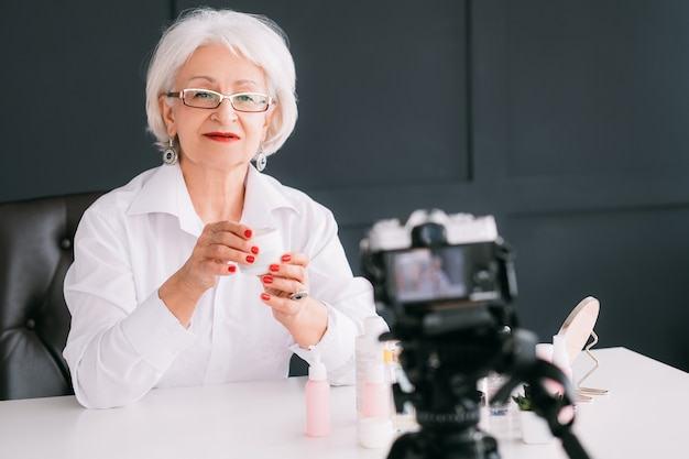Blogger senior de estilo de belleza. mujer de negocios exitosa. elegante anciana haciendo video tutorial.