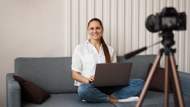 Blogger sonriente graba un nuevo video. se sienta en el sofá de su casa y sostiene una computadora portátil. concepto de blog de negocios positivo.