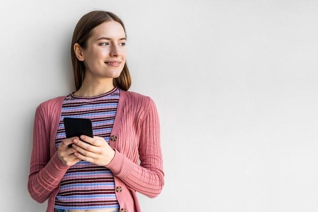 Blogger sosteniendo su teléfono con espacio de copia