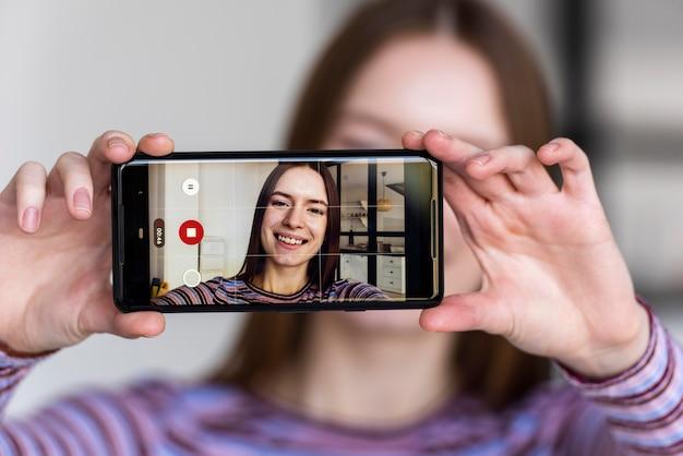 Blogger sosteniendo el teléfono y grabándose a sí misma
