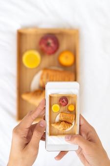 Blogger tomando fotos de comida, disparando desayuno en la cama en el hotel en el teléfono móvil, bandeja con jugo, fruta y croissant en sábanas blancas