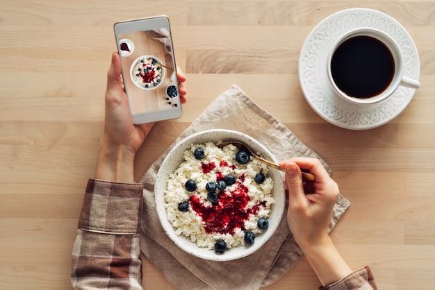 Blogger tomando fotos de comida, disparando el desayuno en el teléfono móvil, cuenco de cuajada casera con mermelada, frambuesas, arándanos y taza de café