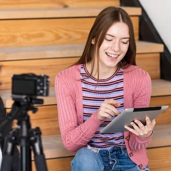 Blogger usando tableta frente a cámara