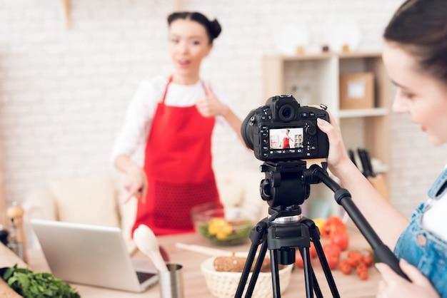 Los bloggers culinarios leen desde una computadora portátil con una chica.