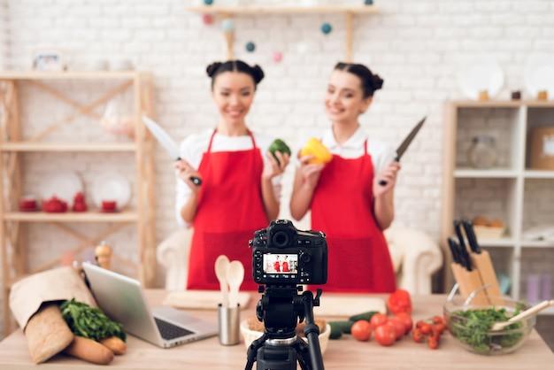 Los bloggers culinarios sostienen pimientos y cuchillos.