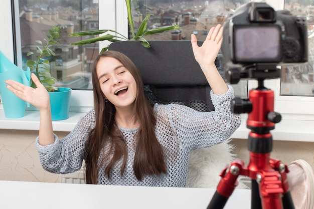 Una bloguera lleva un video blog, se comunica con los suscriptores frente a la cámara