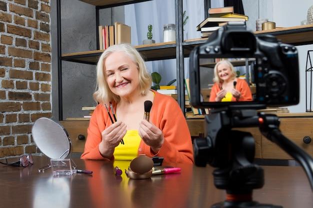 La bloguera de una mujer mayor que la graba hace un video en línea con una cámara,