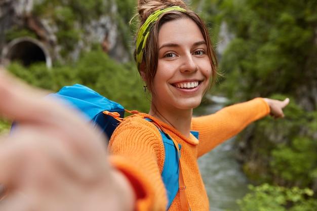Bloguera positiva graba videos en línea mientras explora la naturaleza y señala la distancia