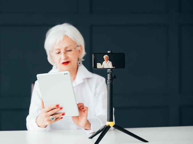 Bloguera senior. coach de negocios online. elegante mujer mayor en streaming de vídeo.