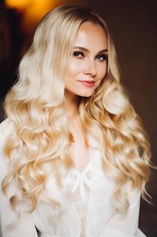 Blondie hermosa novia sonriendo en el dormitorio