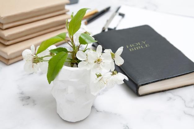 Blooming cherry en un jarrón de calavera en el fondo de la biblia en el escritorio
