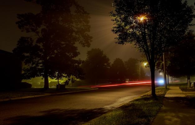Bloque de apartamentos en la calle de la ciudad de noche vacía cubierta de niebla