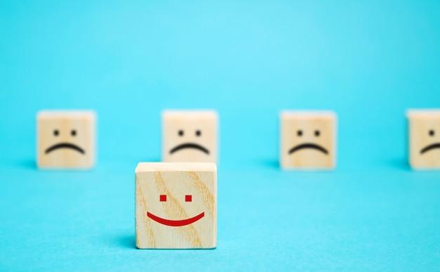 Un bloque con una cara positiva se destaca del resto de las emociones negativas.
