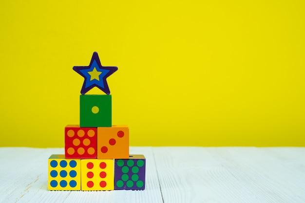 Bloque cuadrado rompecabezas de juguete en la mesa con fondo amarillo