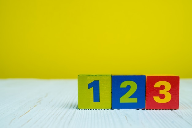Bloque cuadrado rompecabezas número 1 2 y 3 en la mesa con amarillo