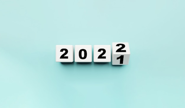 Bloque de cubo blanco volteando de 2021 a 2022 sobre fondo azul, preparación para feliz navidad y feliz año nuevo y concepto de representación 3d.