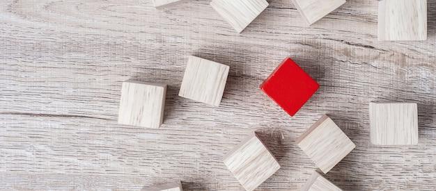 Bloque de cubo rojo diferente de multitud de bloques de madera.
