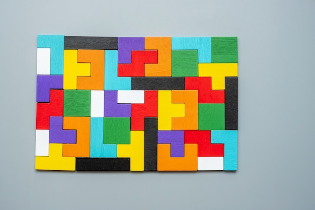 Bloque de forma geométrica con pieza de rompecabezas de madera colorida.