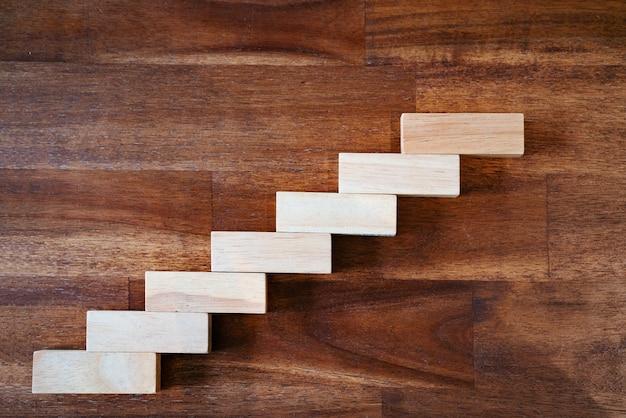Bloque de madera apilado como escalera de paso. concepto de negocio para un crecimiento exitoso.
