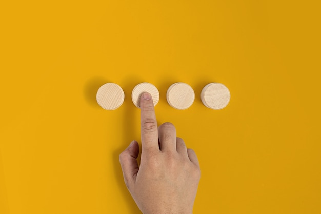 El bloque de madera circular se coloca sobre un fondo amarillo y los gestos de las manos presionan contra el bloque de madera de manera similar a presionar un botón. pancarta con espacio de copia de texto, póster, plantilla de maqueta.