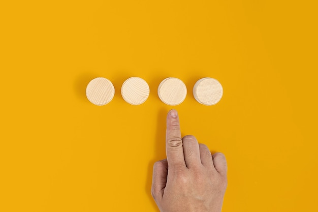 El bloque de madera circular se coloca sobre un fondo amarillo con una mano apuntando al bloque de madera. concepto de bloque de madera, pancarta con espacio de copia de texto, póster, plantilla de maqueta.