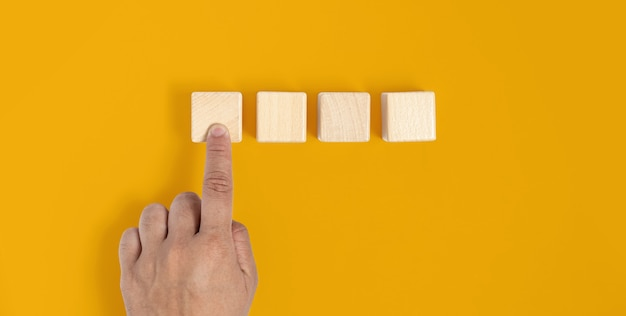 El bloque de madera cuadrado se coloca sobre un fondo amarillo, presionado a mano en el primer bloque de madera similar a presionar un botón. concepto de bloque de madera, pancarta con espacio de copia de texto, póster, plantilla de maqueta.