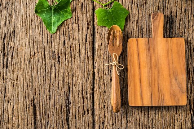 Bloque de madera y cuchara y tenedor sobre fondo de madera