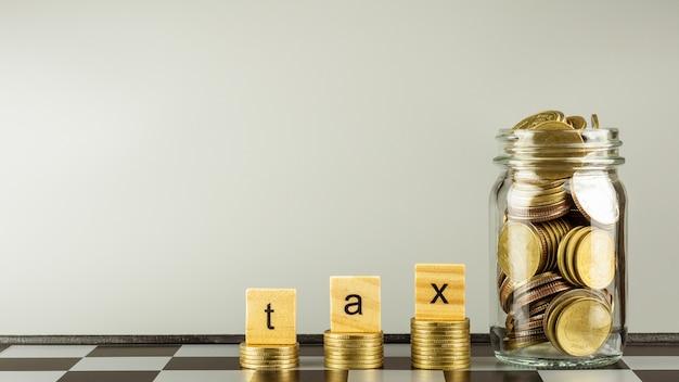 Bloque de madera del impuesto en monedas de oro de la pila. - ahorro de dinero por concepto de contabilidad financiera.