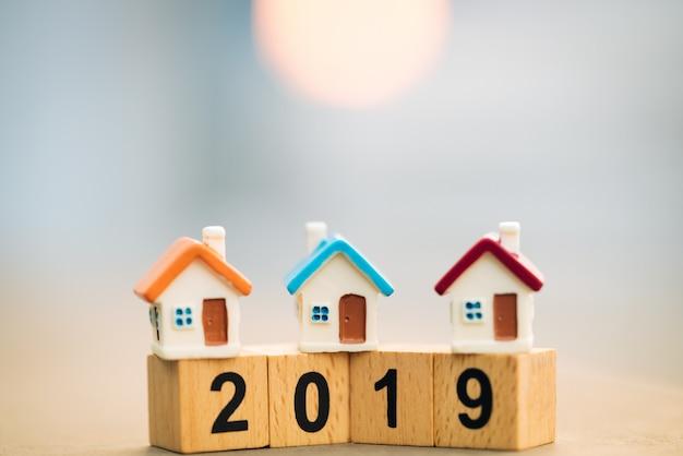 Bloque de madera palabra 2019 año nuevo y casa en la parte superior de la pila de monedas.