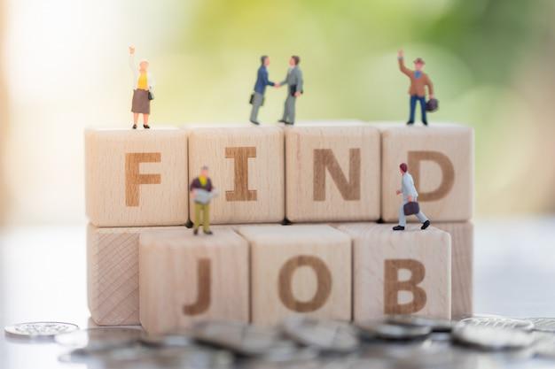 Bloque de madera palabra encontrar trabajo y hombre de negocios