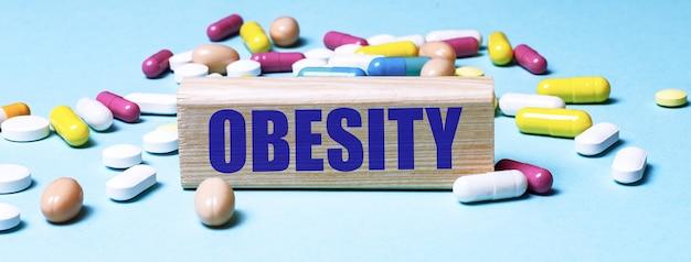 Un bloque de madera con la palabra obesidad se encuentra sobre una superficie azul entre píldoras multicolores. concepto medico