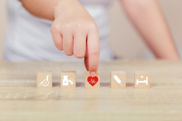 Bloque de madera del seguro médico que apila con la asistencia sanitaria del icono médica.