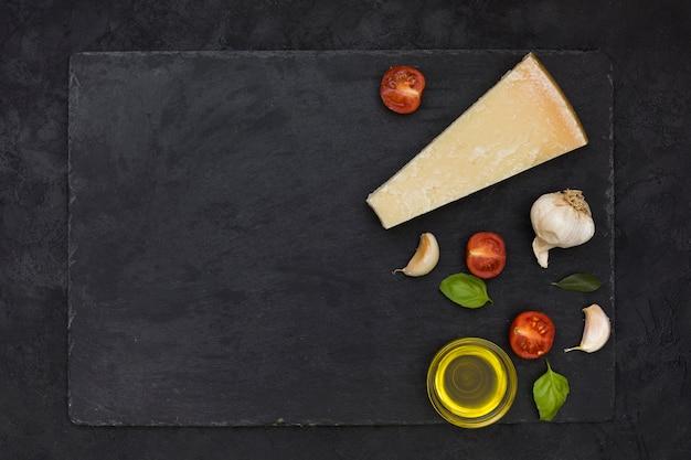 Bloque de queso; dientes de ajo; albahaca y tomates a la mitad con aceite de oliva en roca de pizarra sobre el fondo negro