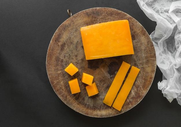 Bloque, rodajas y cubitos de queso cheddar