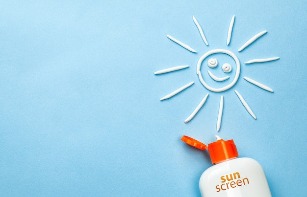 Bloqueador solar. crema en forma de sol sobre fondo azul con tubo blanco.