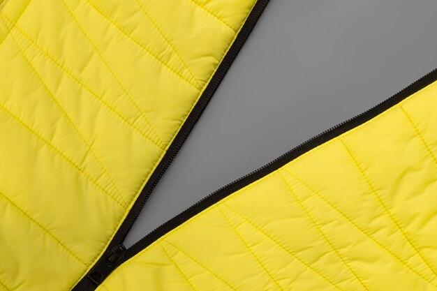Bloqueo de cremallera estirado de chaqueta amarilla sobre fondo gris. colores del año 2021, illuminating y ultimate grey