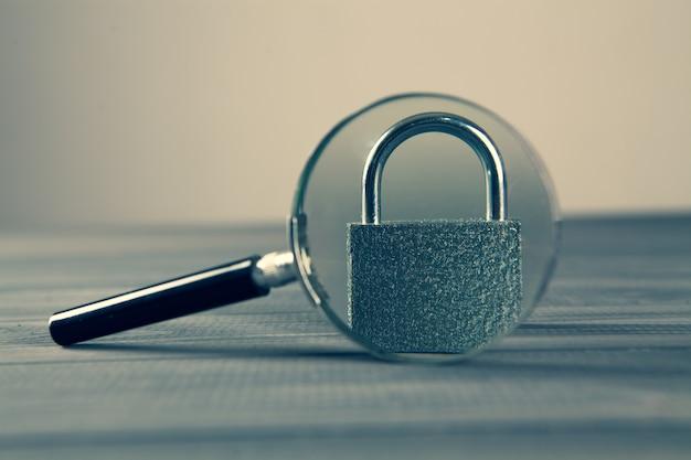 Bloqueo y lupa sobre una mesa de madera gris. concepto de seguridad de búsqueda