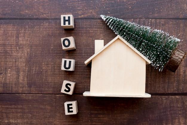 Bloques de casa de palabra con casa de madera y árbol de navidad en mesa