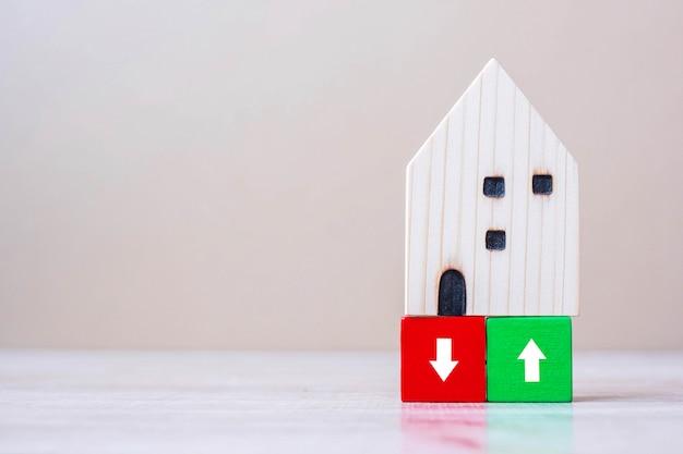 Bloques de cubo financiero con modelo de casa de madera en el fondo de la tabla.