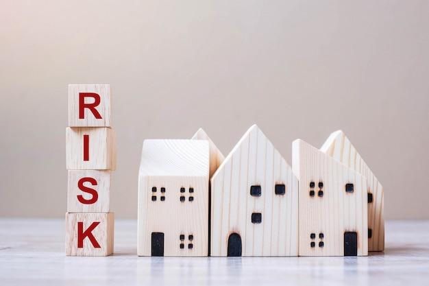 Bloques de cubo de riesgo con modelo de casa de madera en el fondo de la tabla.